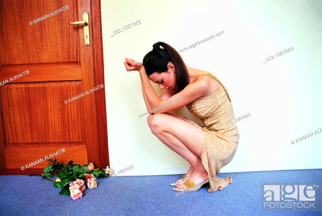 Stock Photo: Sad woman with flowers.