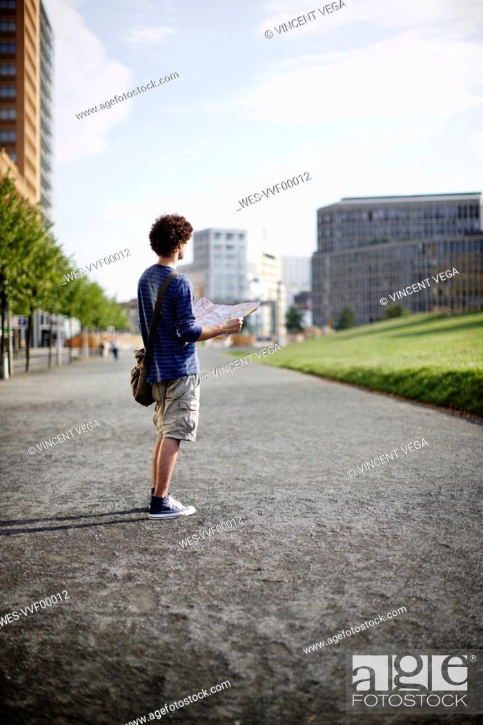 Stock Photo: Germany, Berlin, Young man holding city map.