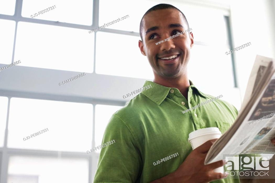 Stock Photo: Businessman standing in office holding coffee cup and newspaper.