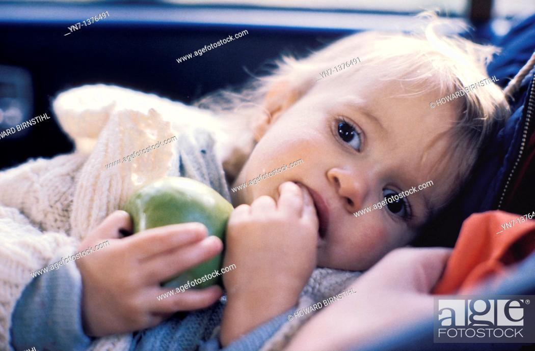 Stock Photo: baby lying in the back seat of a car holding a green apple lost in thought.