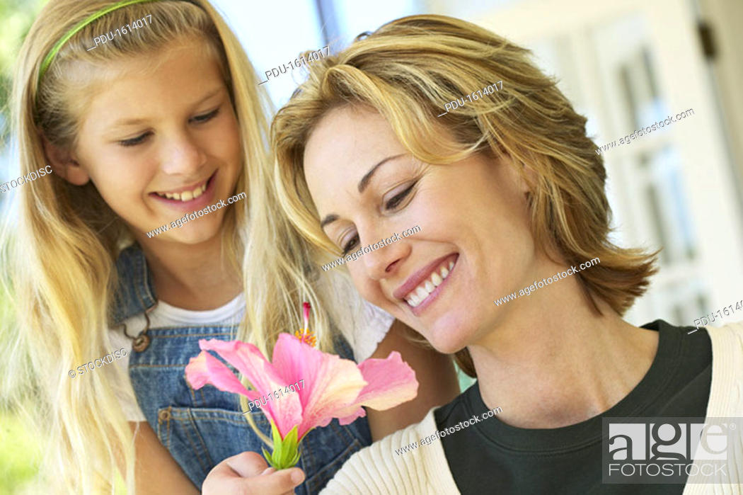 Stock Photo: daughter (10-11) giving a flower to her mother.