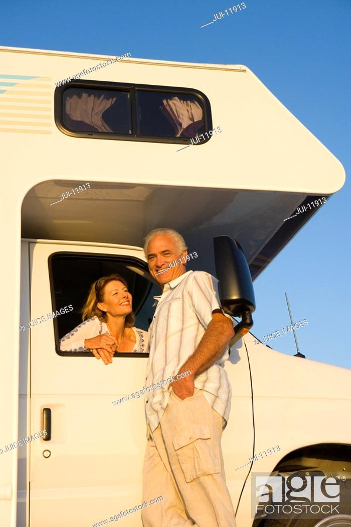Stock Photo: Mature woman looking out window of motor home at husband, portrait of man smiling, low angle view.