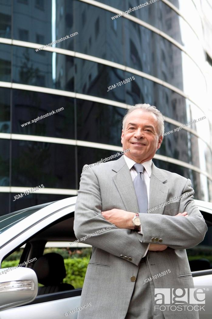 Stock Photo: Senior businessman standing near the car with arms crossed and smiling.
