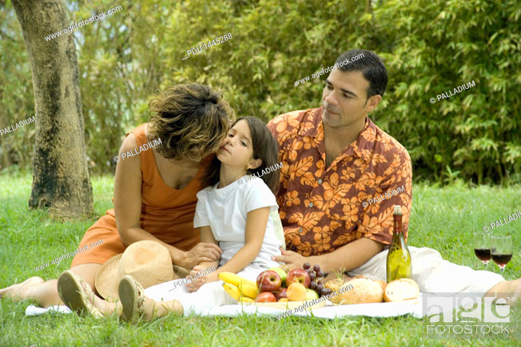 Stock Photo: Portrait of couple and girl having a picnic in the park, with woman kissing girl.