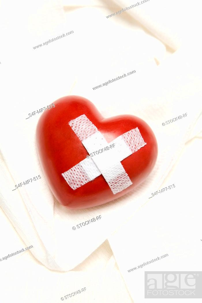 Stock Photo: Heart glued with band aid.