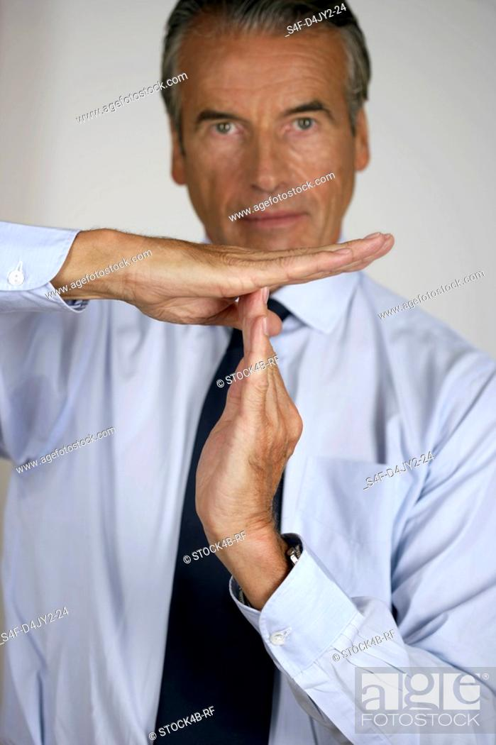Stock Photo: Senior businessman showing a hand signal Time out.