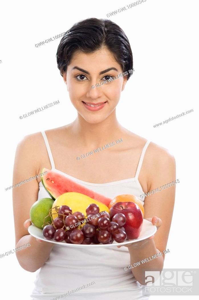 Stock Photo: Portrait of a woman holding a plate of assorted fruits.