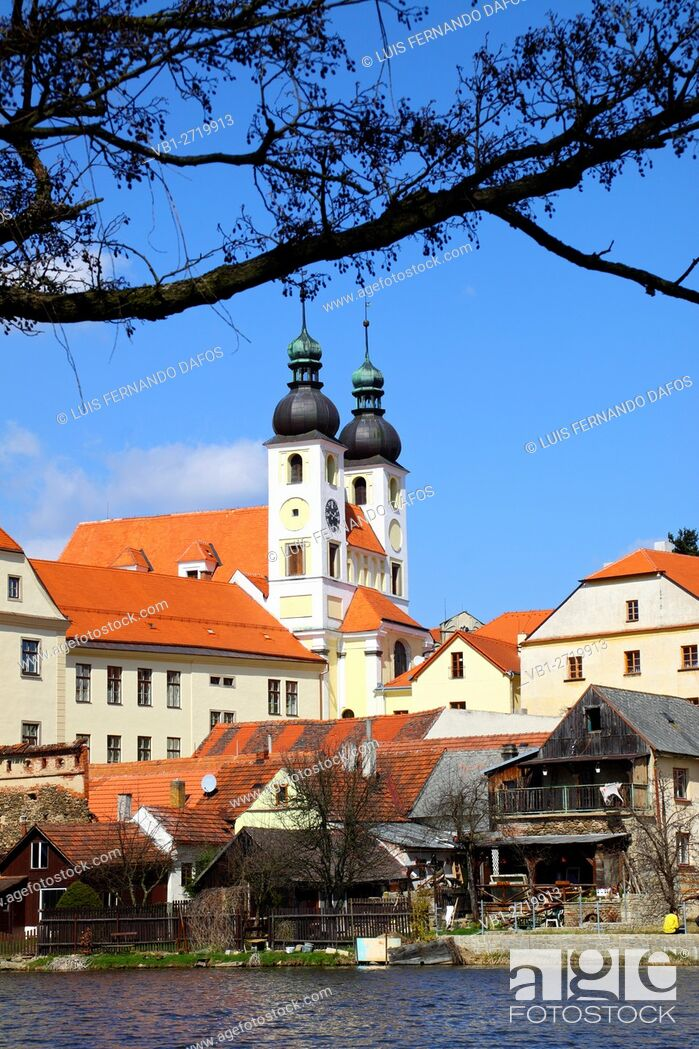Stock Photo: Holy Name of Jesus church and houses by the shore of the Ulicky pond, Telc, Czech Republic.