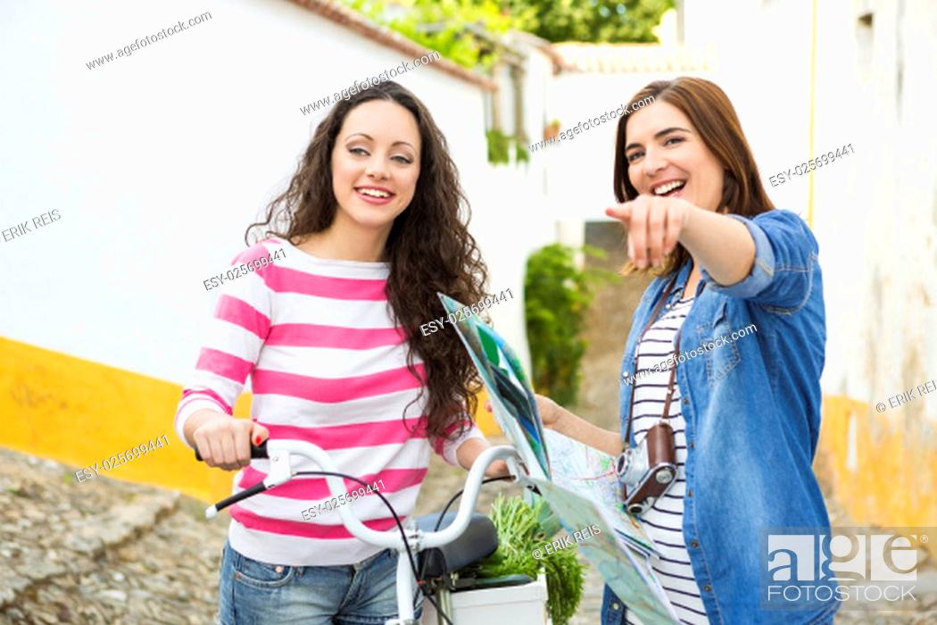 Photo de stock: Two beautiful female tourists searching a place on the map.