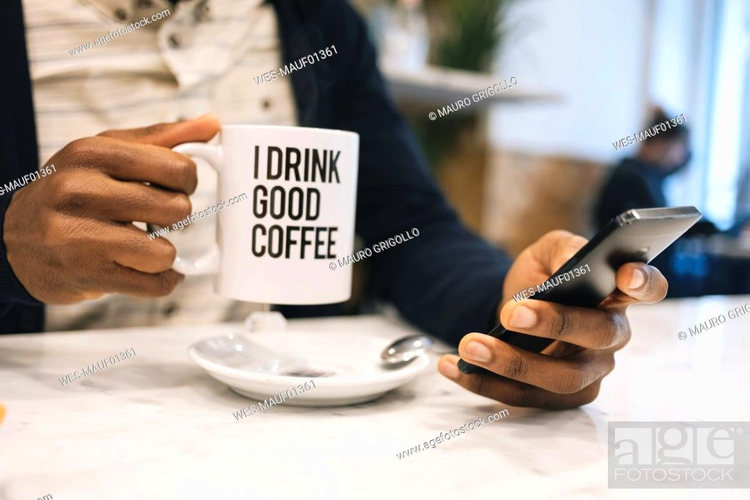 Imagen: Close-up of man with cup of coffee in a cafe using cell phone.