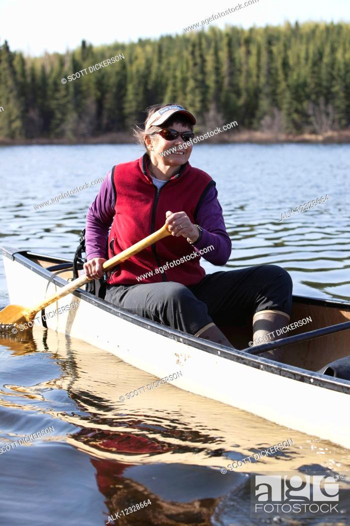 Photo de stock: Woman steering a canoe in the Swanson Lake area, Kenai Peninsula, South-central Alaska; Alaska, United States of America.