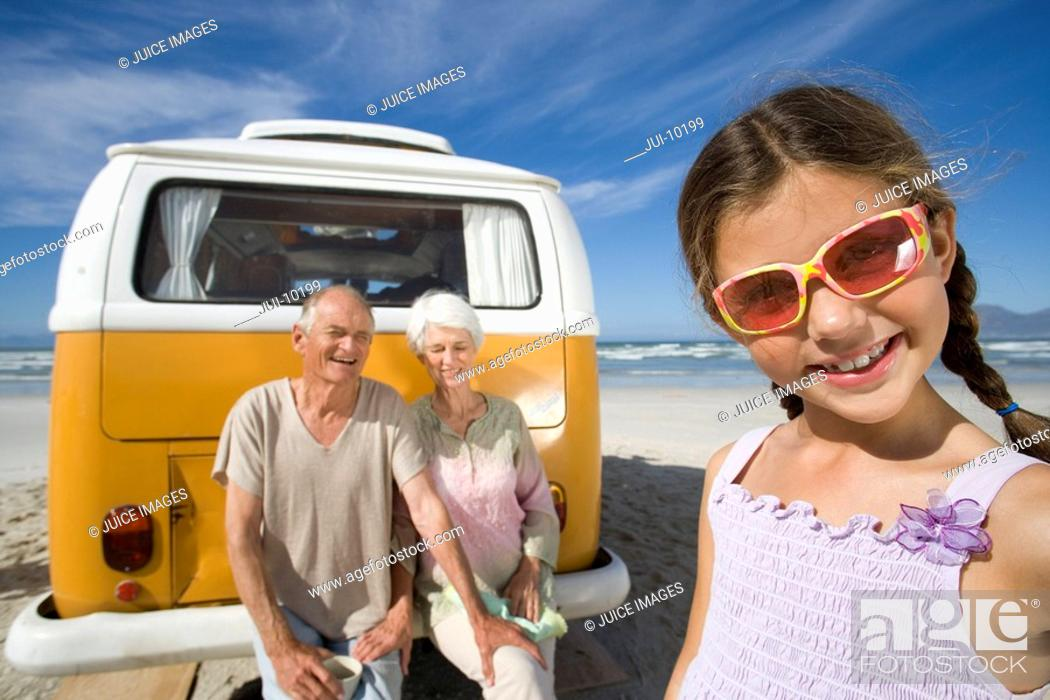 Stock Photo: Girl 7-9 wearing sunglasses on beach by grandparents on back of camper van, smiling, close-up.