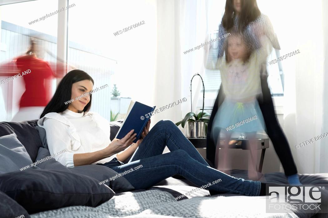 Stock Photo: Girls jumping on sofa while mother reading a book.