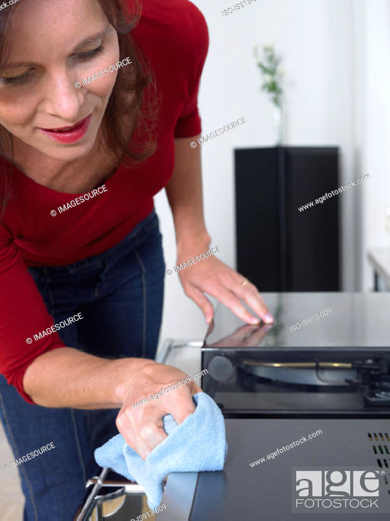 Stock Photo: Woman dusting stereo.