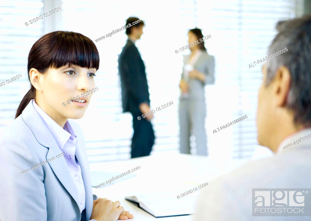 Stock Photo: Business colleagues conversing in office.