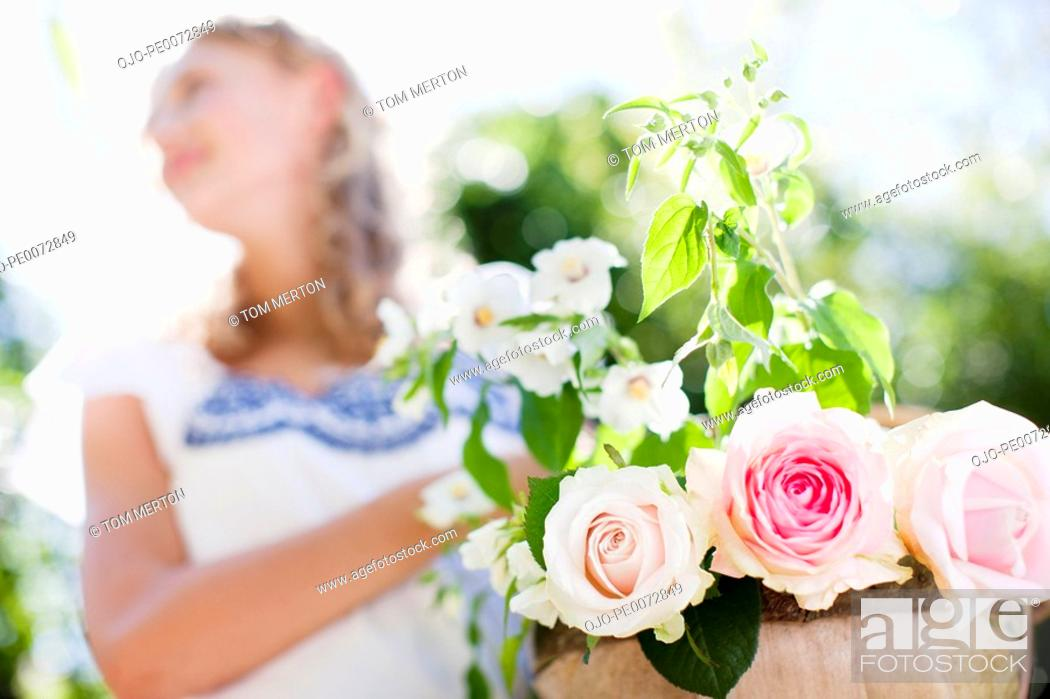 Stock Photo: Close up of woman holding flowerpot with roses.