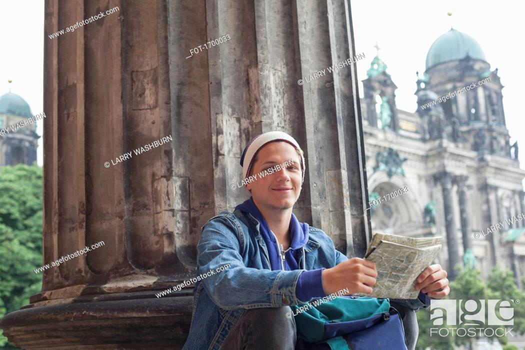Imagen: Low angle portrait of young male tourist sitting with map at Altes Museum, Berlin, Germany.