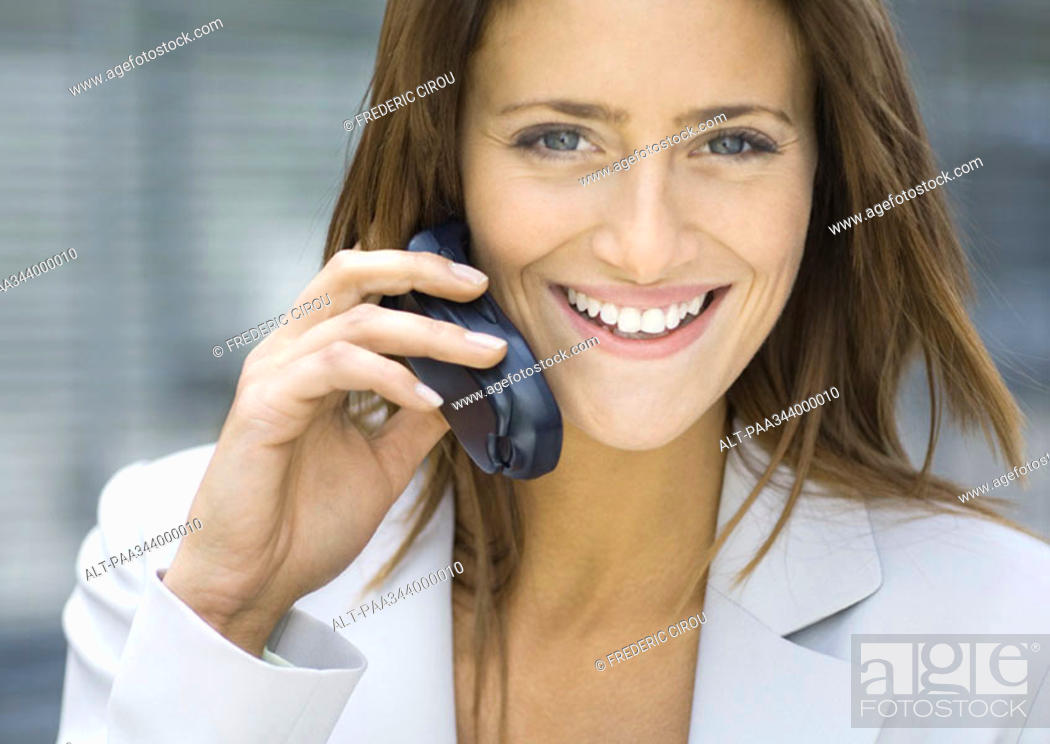 Stock Photo: Businesswoman using cell phone, smiling.