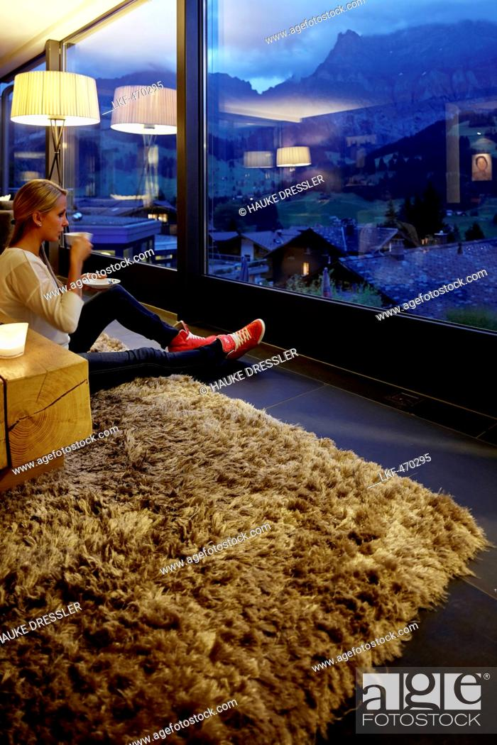 Stock Photo: Woman sitting on floor in a hotel winter garden while enjoying view in the evening, Adelboden, Canton of Bern, Switzerland.