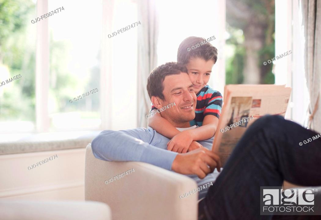 Stock Photo: Father and son reading newspaper together.