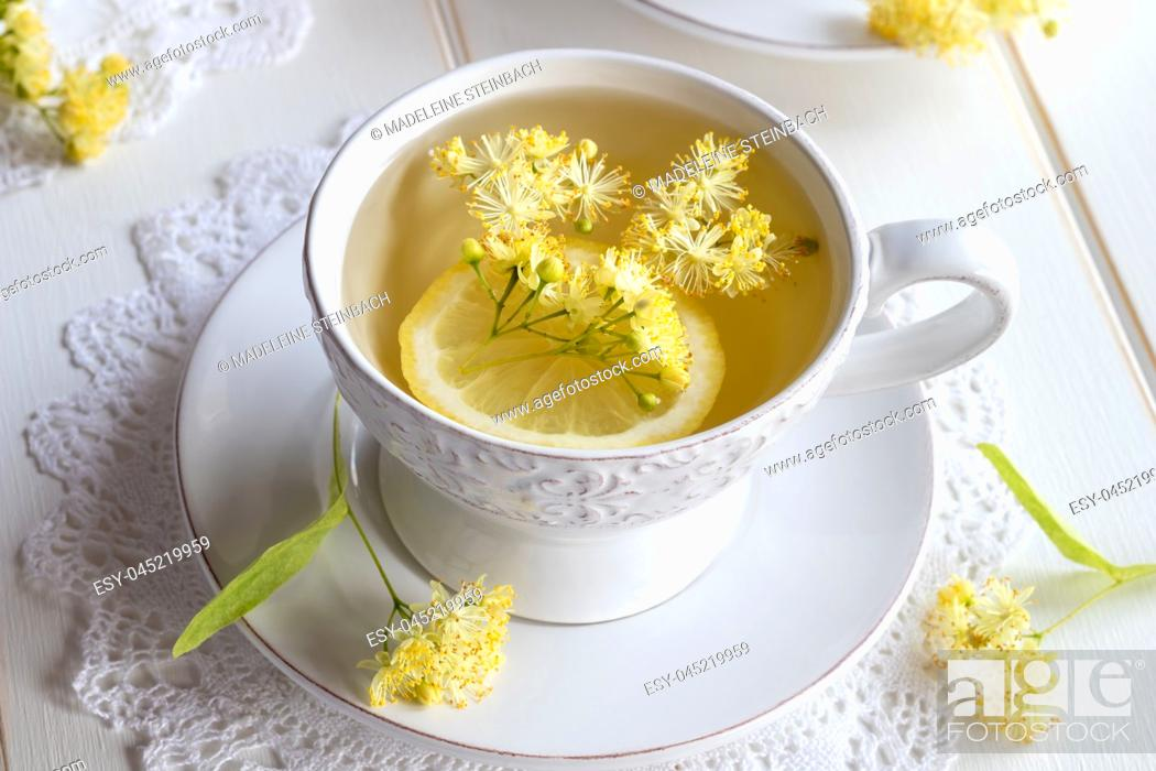 Stock Photo: A cup of herbal tea with fresh linden flowers and lemon.