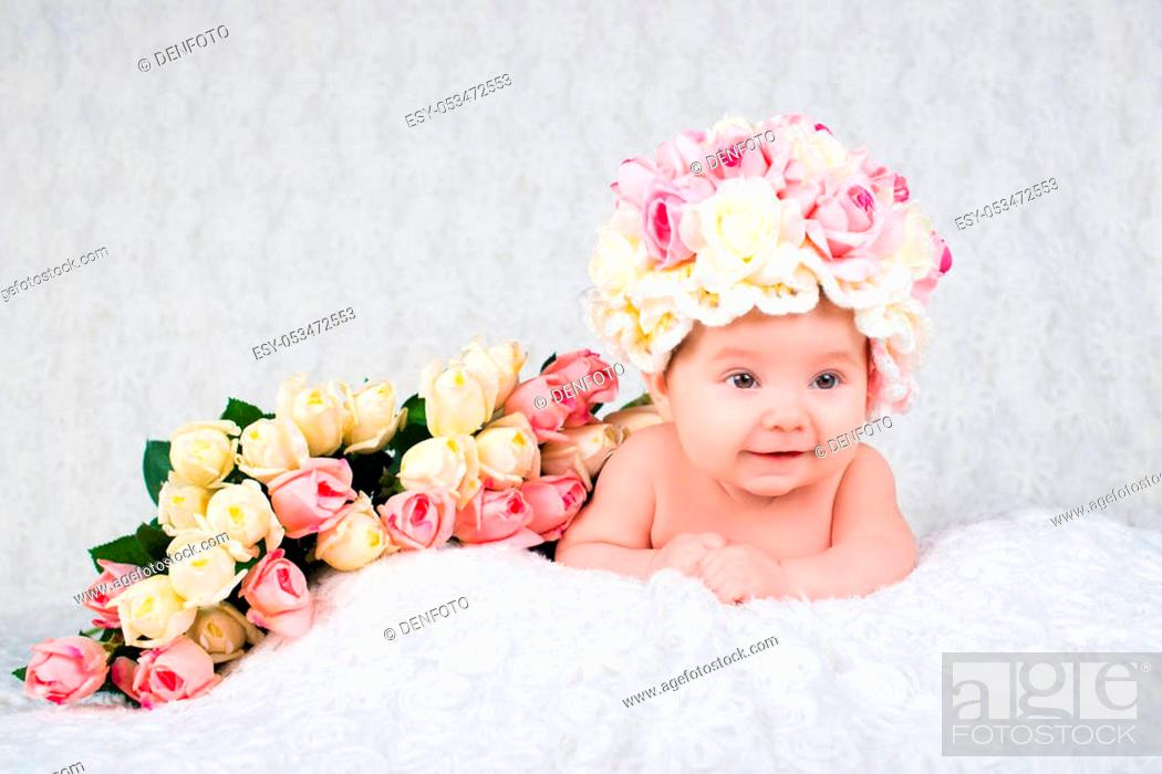Stock Photo: A newborn baby girl in the hat of the rose smiles. Portrait on a white background.