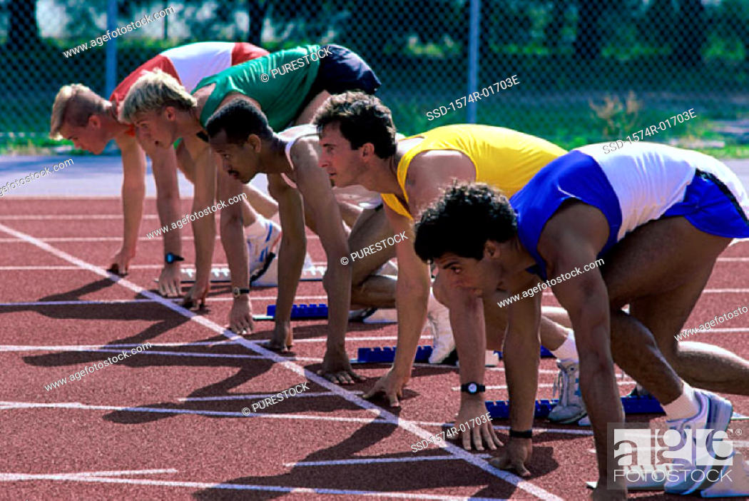 Stock Photo: Side profile of male runners at the starting line.
