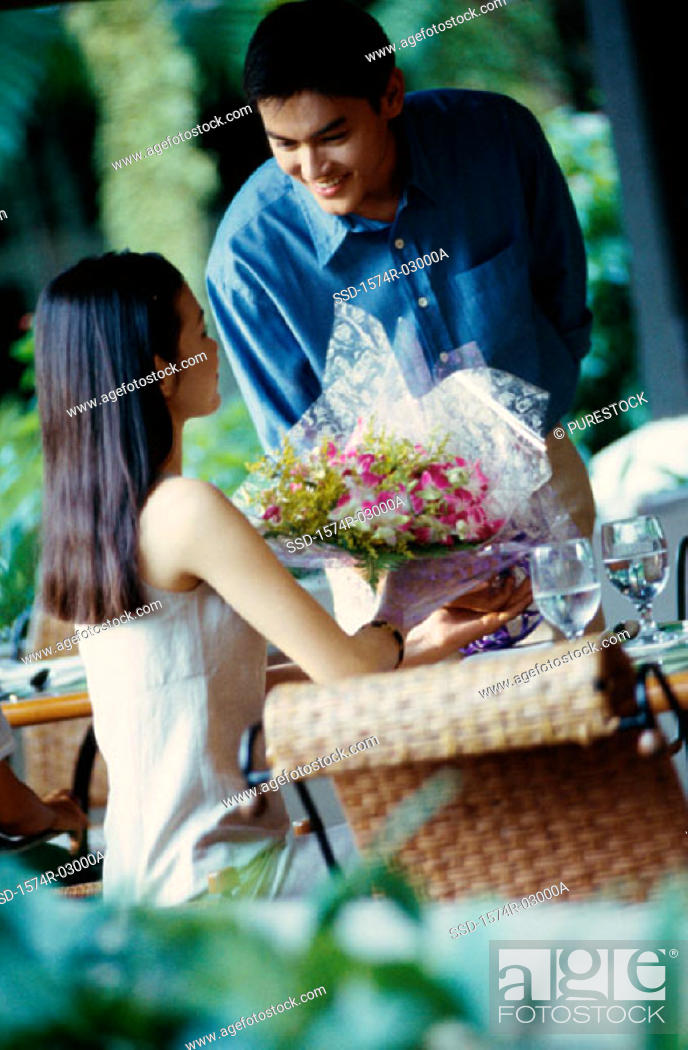 Stock Photo: Young man giving a bouquet of flowers to a young woman.