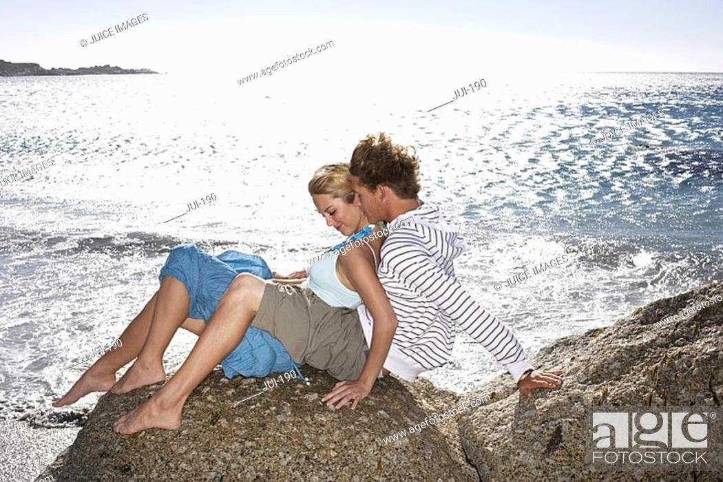 Stock Photo: Teenage couple 17-19 sitting on rocky beach in bright sunlight, girl in boy's lap, smiling.