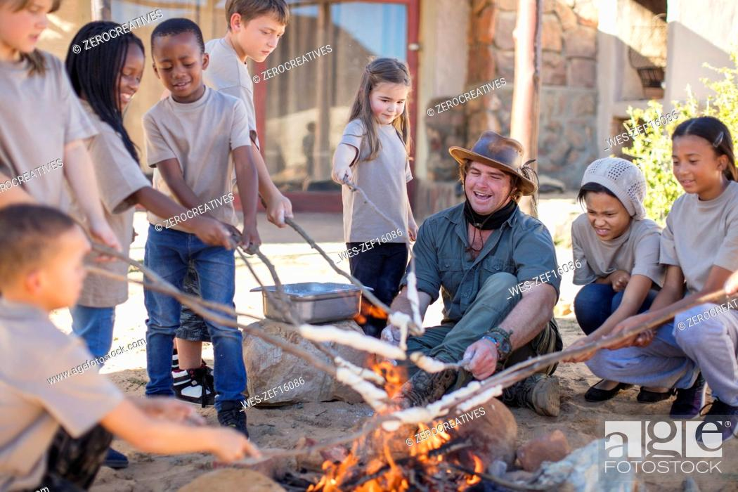 Stock Photo: Children and guide roasting twist bread at camp fire.