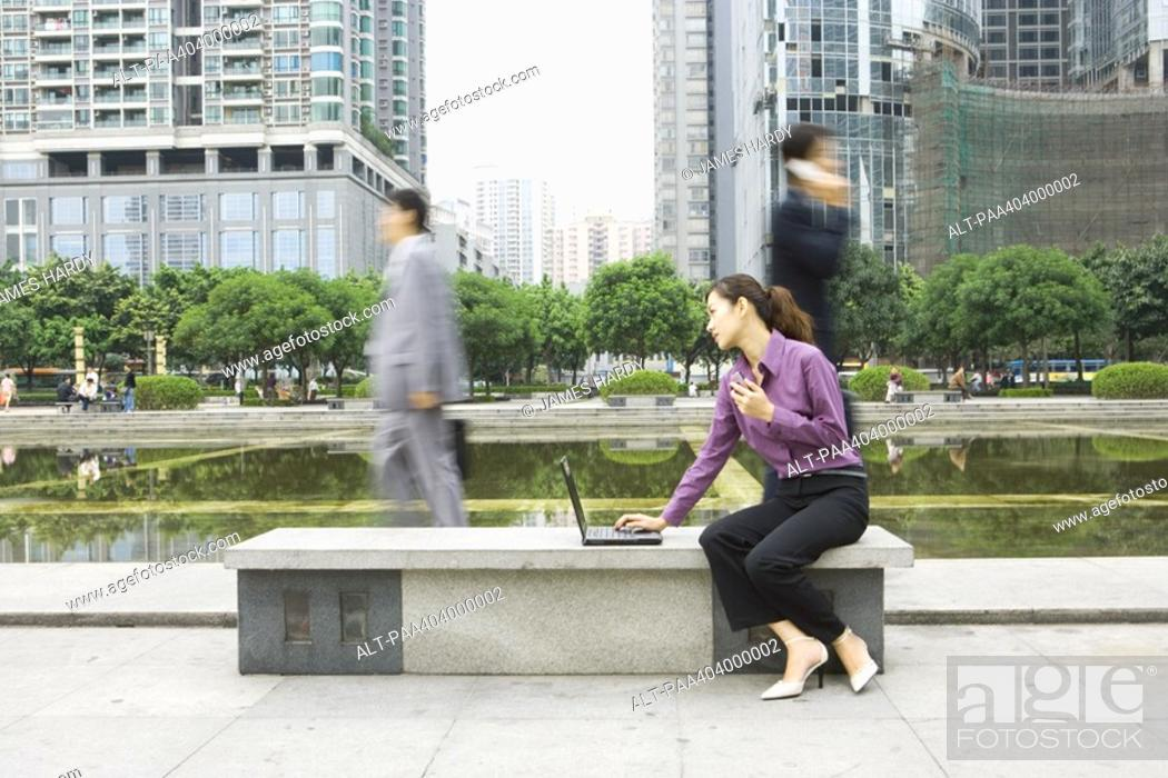 Stock Photo: Young woman using laptop outdoors on office park bench.