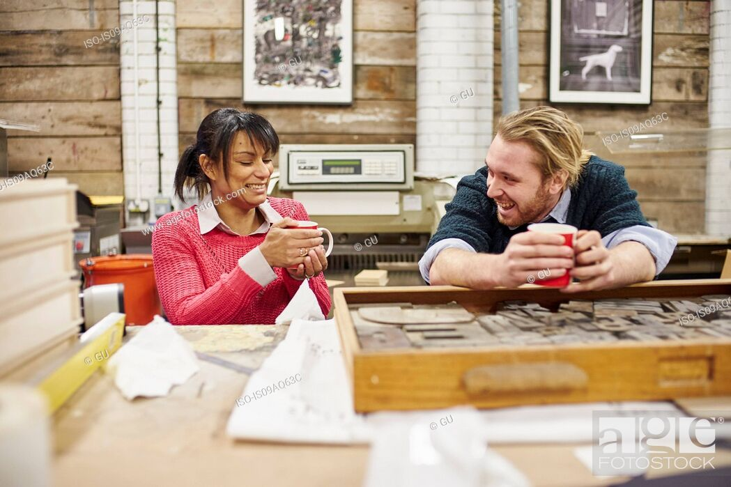 Stock Photo: Male and female printers chatting and drinking coffee in traditional print workshop.