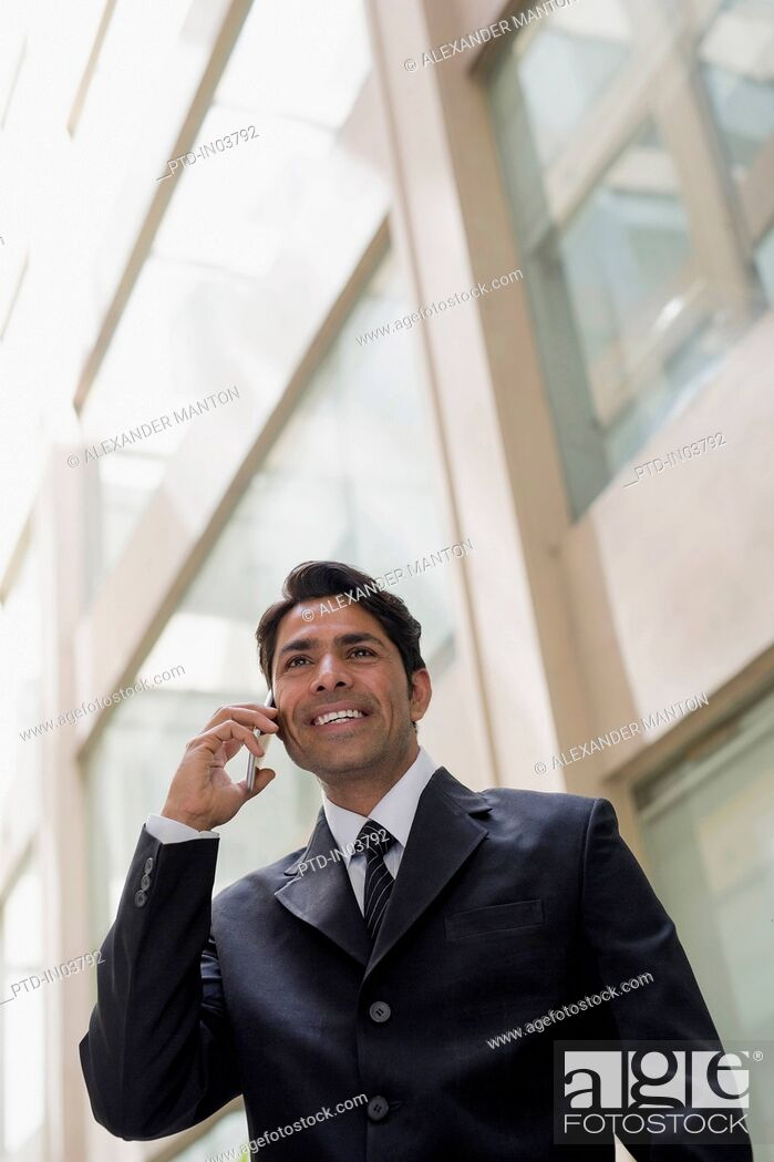 Stock Photo: India, Businessman standing outside office building, talking on mobile phone.