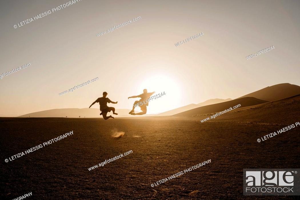 Stock Photo: Namibia, Namib desert, Namib-Naukluft National Park, Sossusvlei, two men jumping at Dune 45 at sunrise.