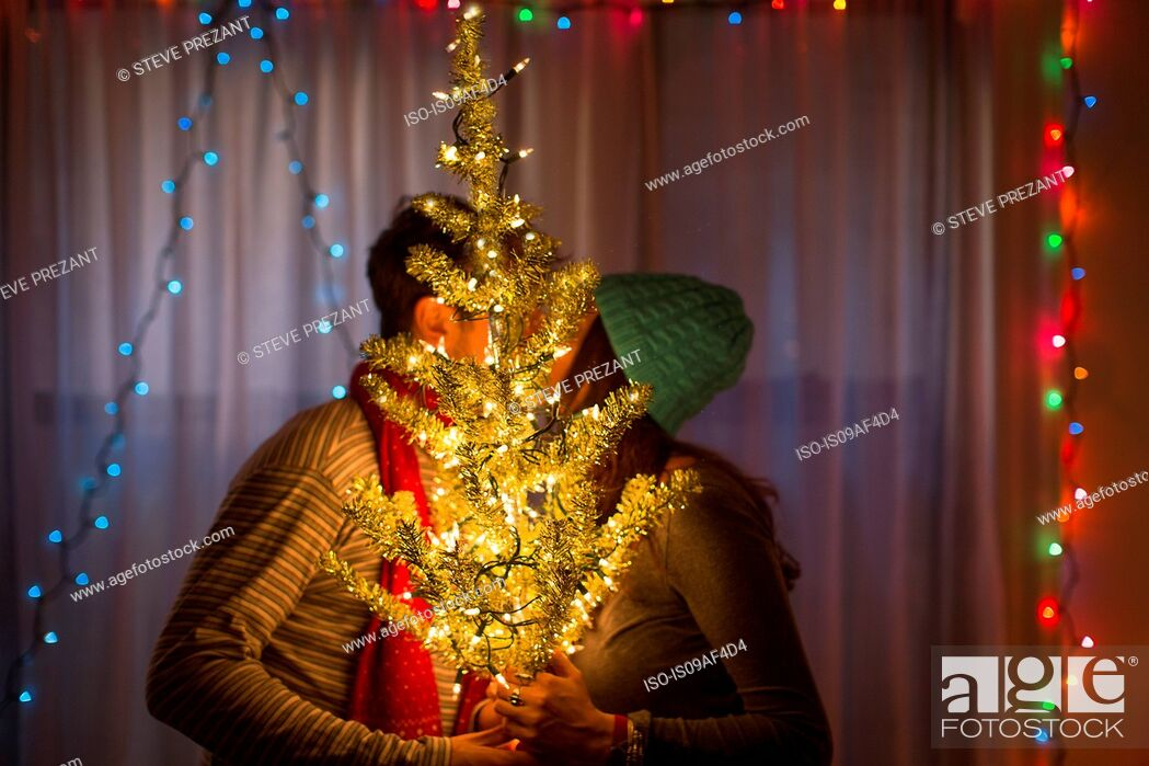 Stock Photo: Young couple kissing behind illuminated christmas tree.