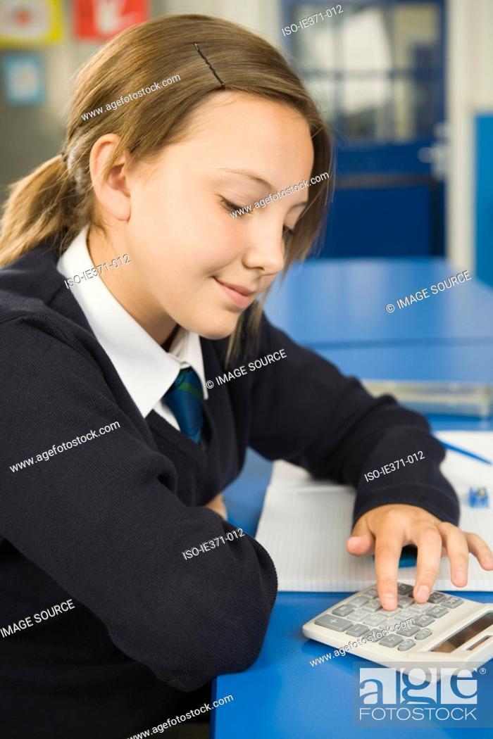Stock Photo: Girl using calculator.