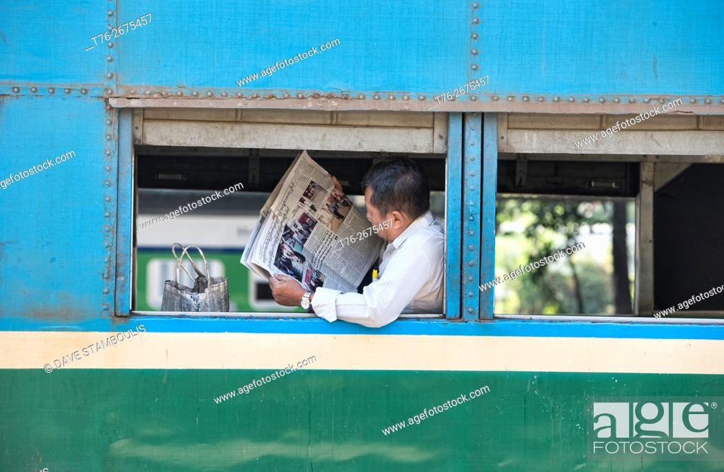 man reading the newspaper on the circular train yangon myanmar