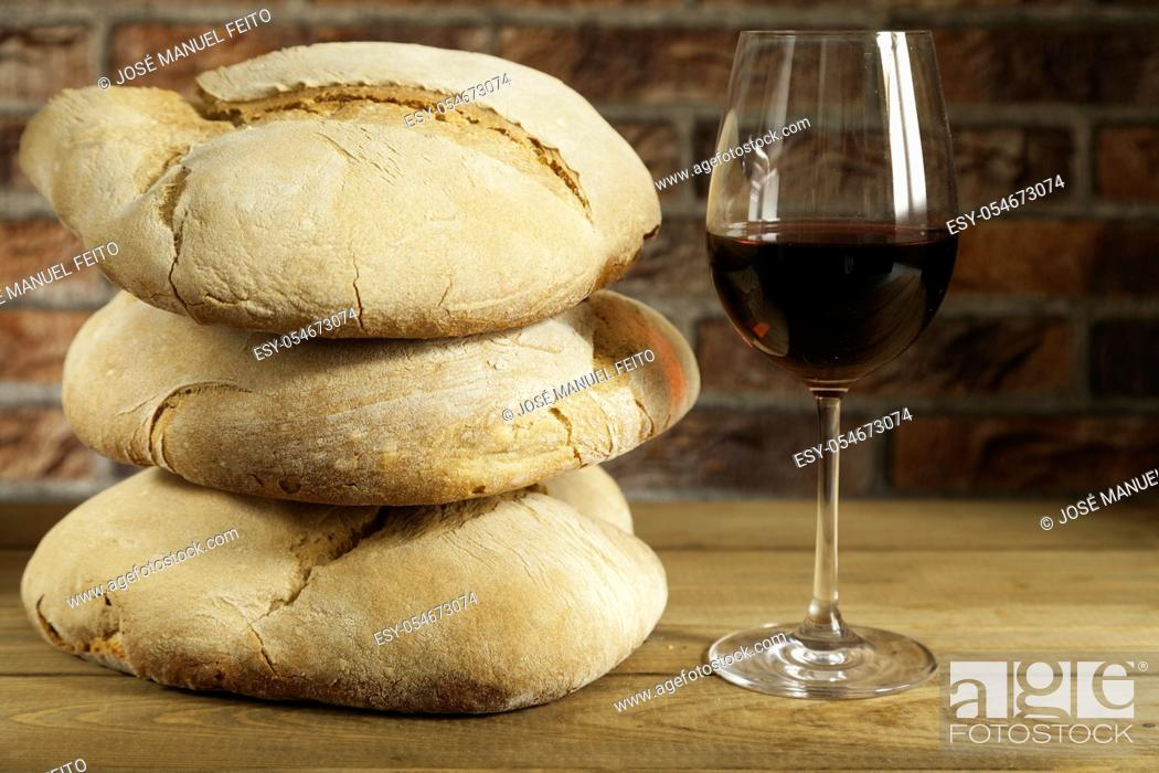 Stock Photo: Glass of red wine and three loaves of rustic bread one on another on wooden table and red brick background.