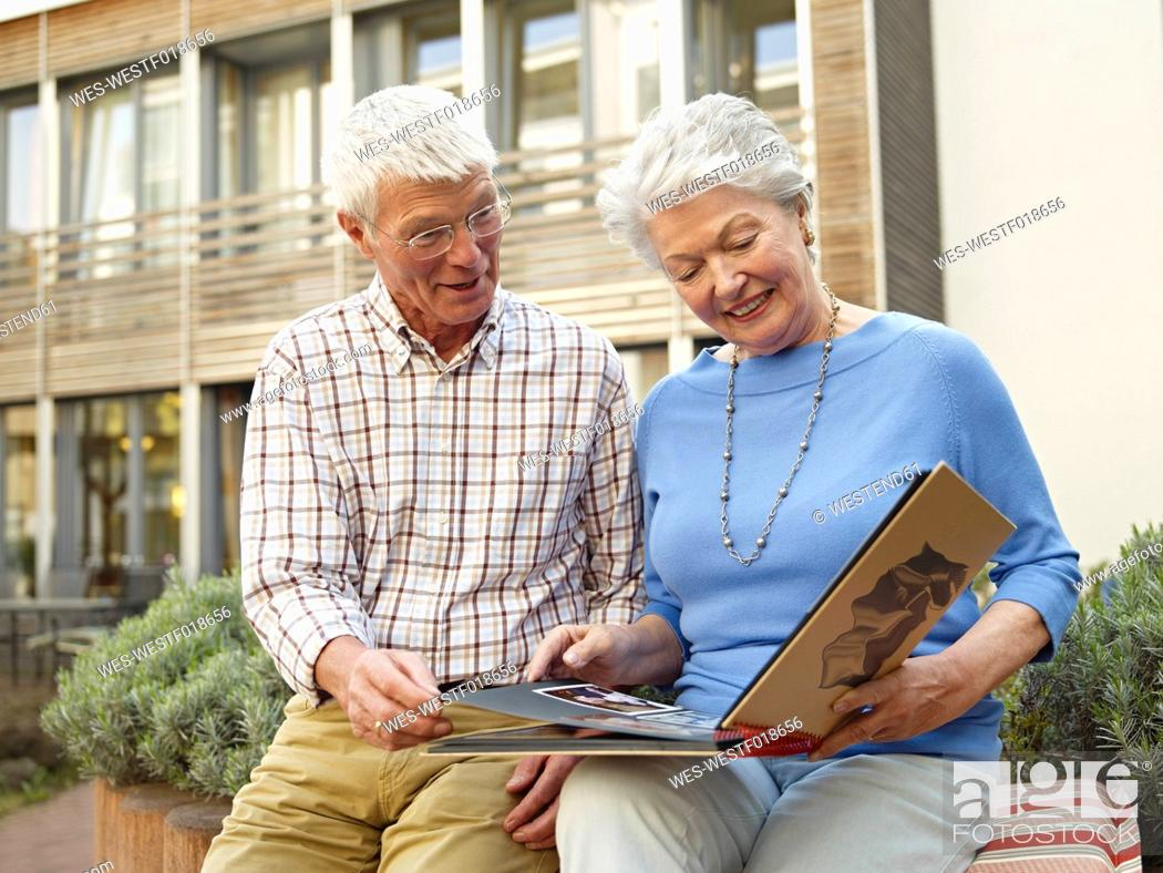 Stock Photo: Germany, Cologne, Senior couple looking photo album in front of nursing home.