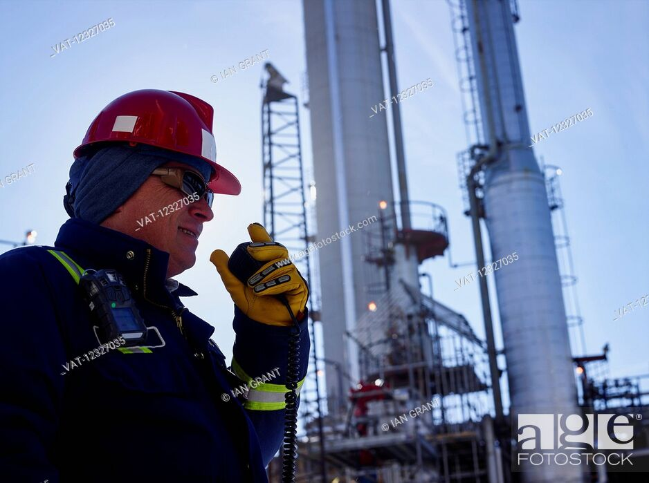 Imagen: Tradesman talking into a radio while working at a refinery; Edmonton, Alberta, Canada.