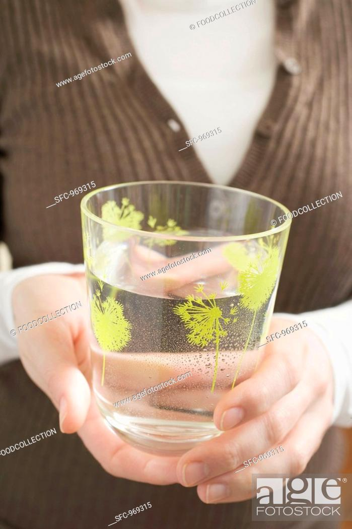 Stock Photo: Woman holding glass of water.
