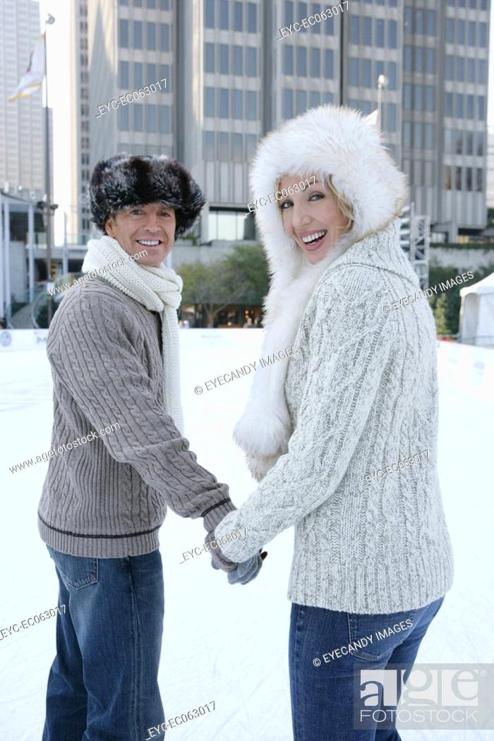 Stock Photo: Mature couple holding hands on an ice skating rink.