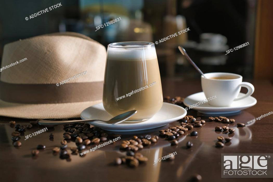 Stock Photo: Delicious aromatic brown beverage with white foam in glass on round saucer standing among roasted coffee beans beside hat with brim on wooden glossy table.