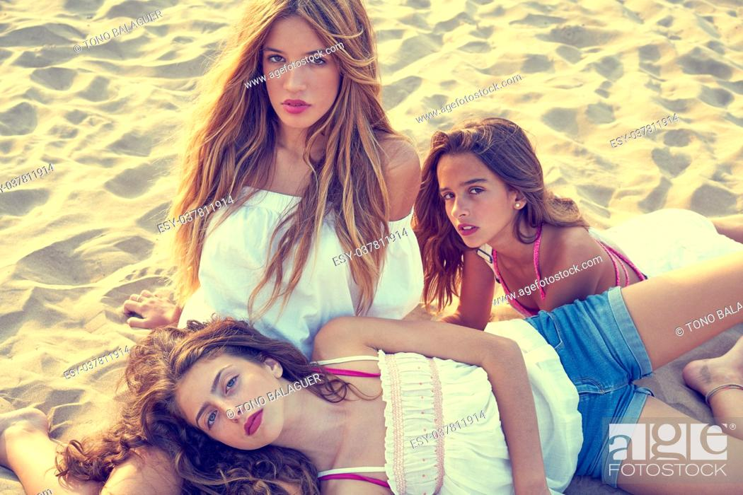 Stock Photo: Best friends teen girls together relaxed on a beach sand at sunset.