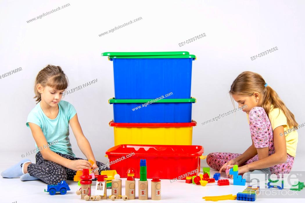 Stock Photo: Two girls play toys, in the middle are boxes with toys.