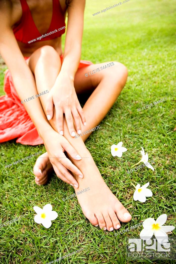Stock Photo: Beauty portrait of a woman in a tropical setting with frangipani at her feet.