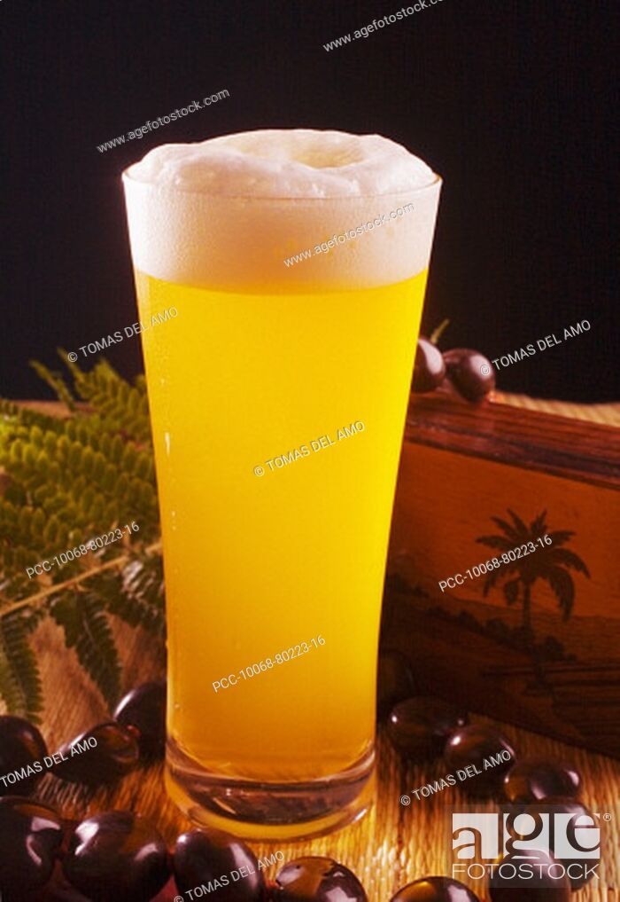 Stock Photo: A tall foaming pint of beer in a tiki bar setting.