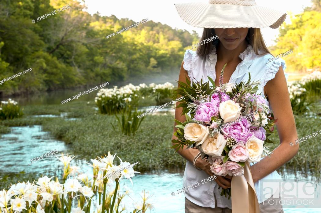 Stock Photo: A partial view of a young woman holding a bouquet of flowers standing in a shallow river with wild Cahaba lillies in the background.