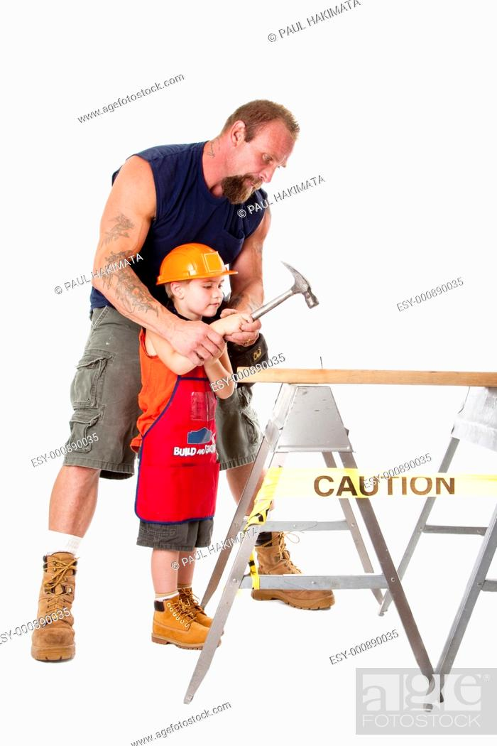 Stock Photo: Caucasian father teaching his cute son how to hild a hammer and hit a nail into a wooden plank, isolated.