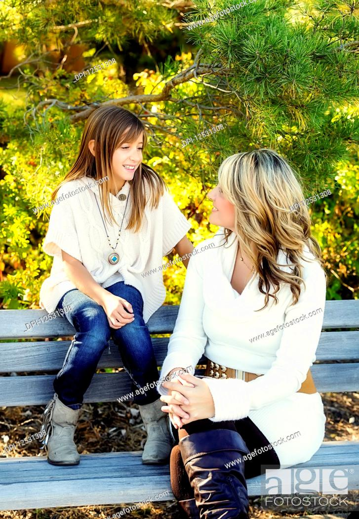 Photo de stock: A mother and daughter sitting on a park bench talking and enjoying each other's company on a warm fall day; Edmonton, Alberta, Canada.